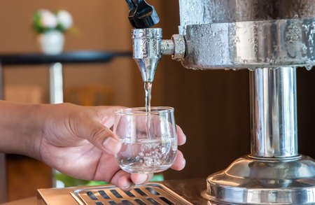 Water is poured into a glass from a manual water dispenser in the hotel restaurant.