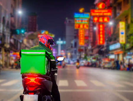 Food delivery drivers are driving deliveries to customers who ordered online at night at Street Food in Chinatown, Thailand.