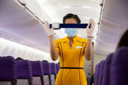 An operator in yellow demonstrates how to fasten seat belts in the aircraft cabin.