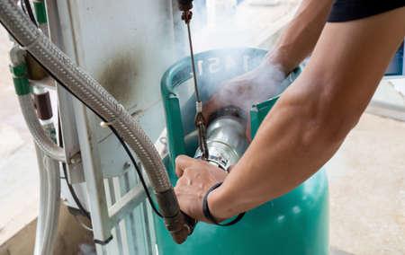 A man working with a gas tank Foto de archivo