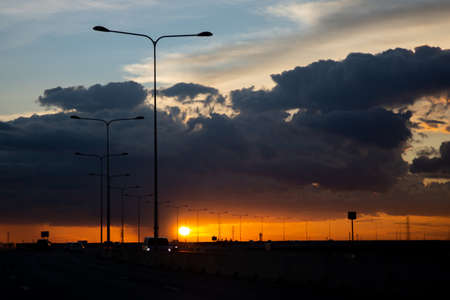 Shadows of cars, lamp posts and evening sunsets on an elevated road.