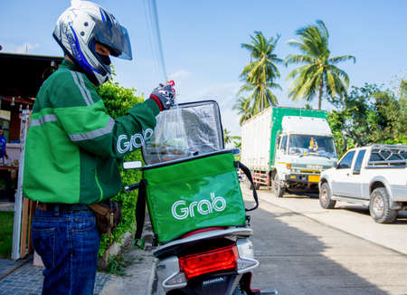 A GrabFood delivery driver is picking up food from the box and delivering it to a customer who ordered online in Thailand on 09-08-2020.