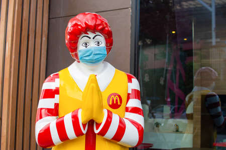 Ronald McDonald, the clown, the mascot from a fast food shop, Jam McDonald wears a medical mask at the storefront. In Bangkok, Thailand on 09-05-2020 Redakční