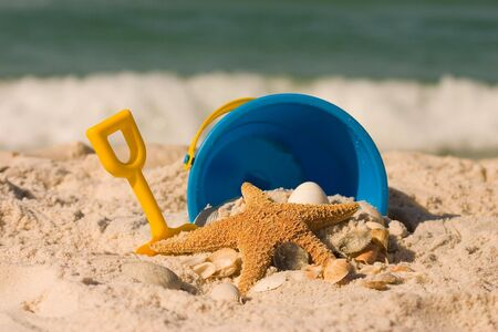 Starfish and kids beach toys in the sand set against waves