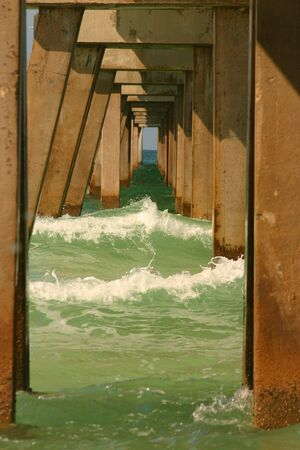 Incoming waves crash against the columns of a pier Stock Photo