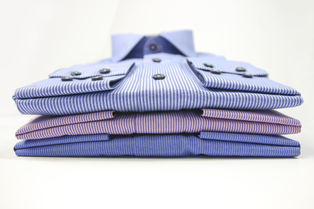 drycleaning: Some colored man shirts folded on white background
