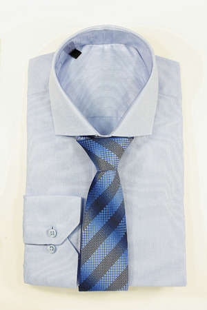 young  cuffs: Blue shirt and striped tie on a white background