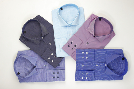 Some colored shirts arranged in a shape on white background