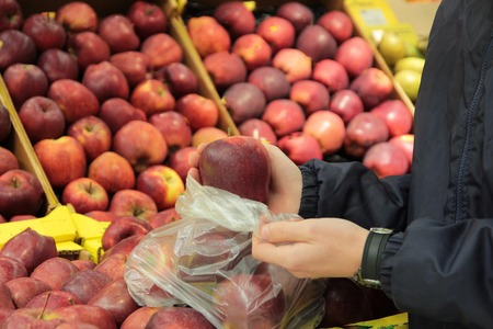 A seller who chooses a red apples Stock Photo