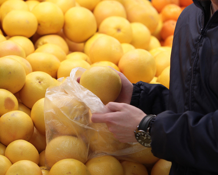 A seller who chooses fruits  vegetables in the supermarket
