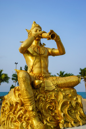 poems: golden statue of Phra Aphai Mani blowing his pipe by the sea