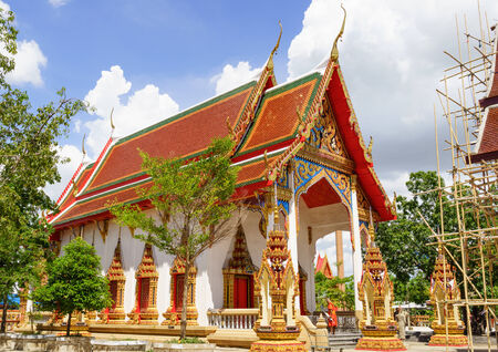 Thai Buddhist temple and a monk before evening prayer photo