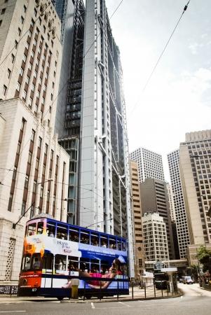 May 2011, Hong Kong - A tram carrying passengers passes by the Bank of China building. photo