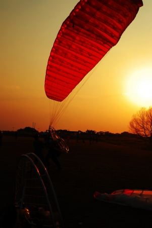 Paramotor lands on a field on sunset background. photo