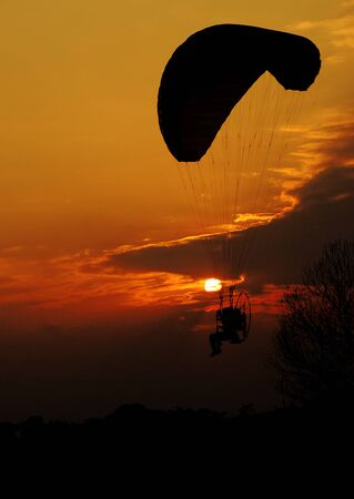 Silhouette image of a paramotor flying at low level on sunset background photo