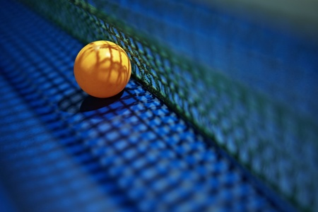 A table tennis  ping pong  ball placed next to the net