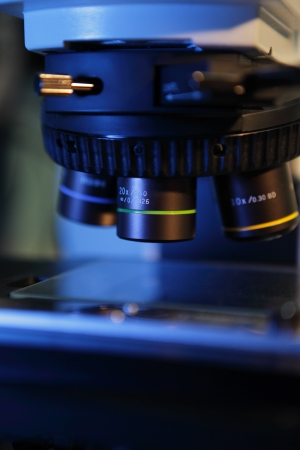 Close up of microscope lenses focused on a specimen in blue light  Stock Photo