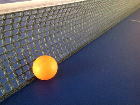 Table tennis ball next to the net. Stock Photo