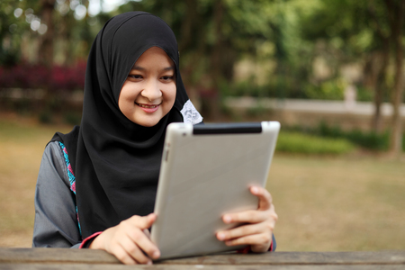 adult indonesia: Beautiful young Muslim woman using tablet at a park
