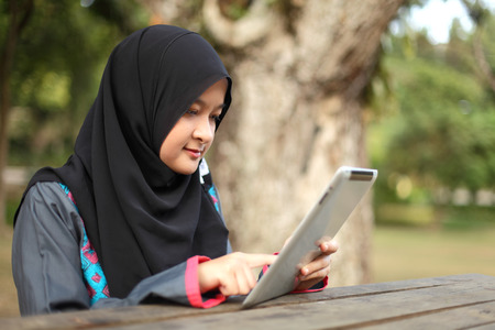 Beautiful young Muslim woman using tablet at a park photo