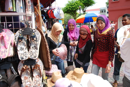 Group of girls looking at hats for sale near the Malacca Stadhuys Tourism Centre
