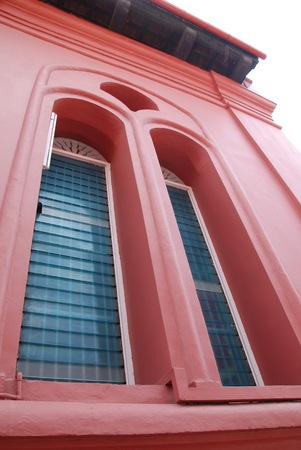 A wide angle view of a window frame on red building photo