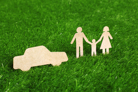 refinance: Family made from cut-out recycle paper on grass Stock Photo