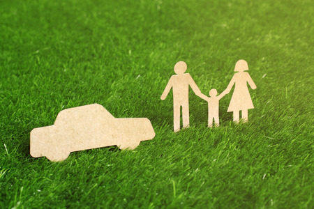 Family made from cut-out recycle paper on grass photo
