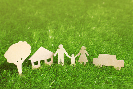 institution: Family made from cut-out recycle paper on grass Stock Photo
