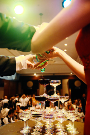 happily: Bride and groom pouring wine into a stacked glass Stock Photo