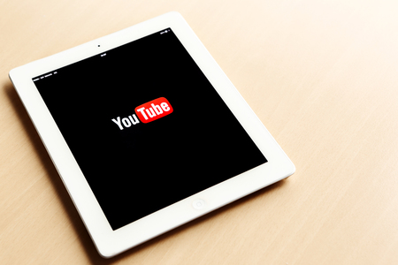 An Ipad tablet with YouTube application on screen lying on desk