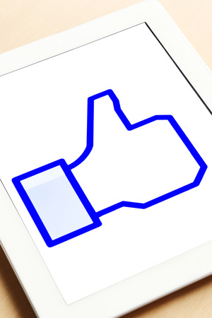 A facebook thumbs up like icon on a tablet screen