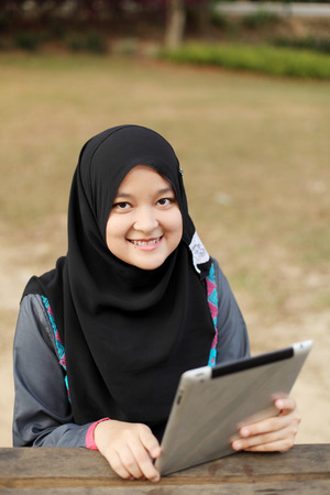 Beautiful muslim woman using tablet at the park photo