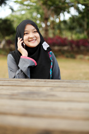 telco: Beautiful muslim woman talking on the phone at the park Stock Photo