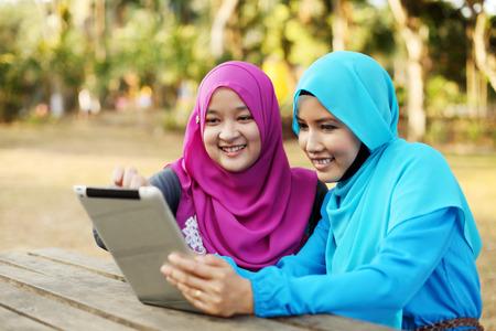 공원에서 태블릿을 사용하여 두 아름 다운 이슬람 여자