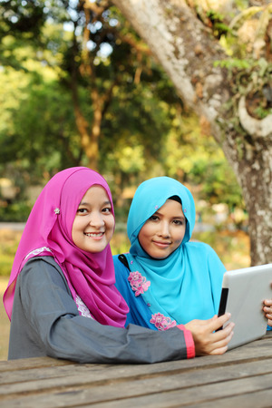 Two beautiful muslim woman using tablet at the park