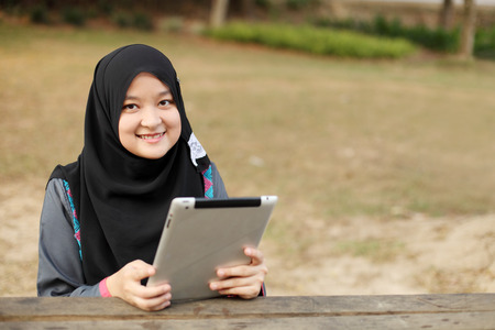 Beautiful muslim woman using tablet at the park