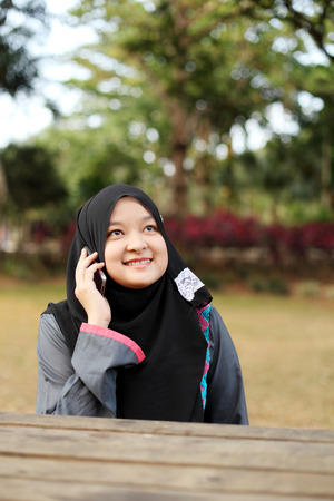 Beautiful muslim woman talking on the phone at the park Stock Photo