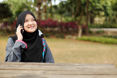 tweeting: Beautiful muslim woman talking on the phone at the park Stock Photo