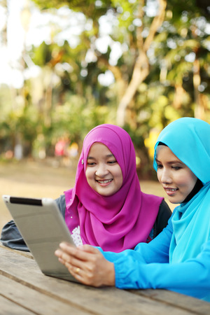 Two beautiful muslim woman using tablet at the park photo