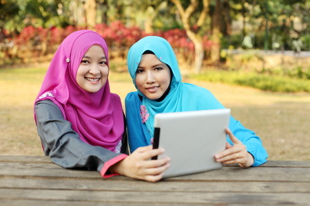 young add: Two beautiful muslim woman using tablet at the park