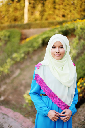 Beautiful muslim woman at the park with flower background photo