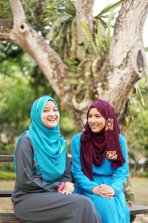 Two beautiful muslim woman hanging out at the park photo