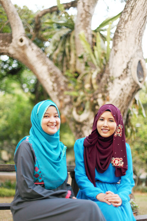 young add: Two beautiful muslim woman hanging out at the park