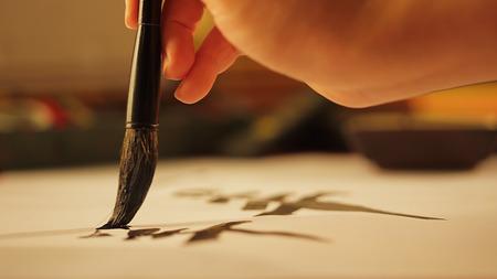 Close up on hand holding brush writing calligraphy Stock Photo