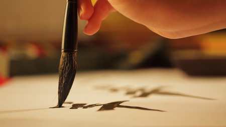 Close up on hand holding brush writing calligraphy Banque d'images