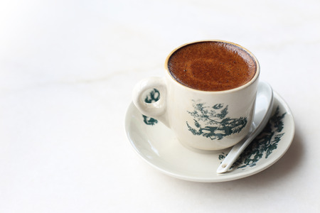 kopitiam: White coffee served in cup with saucer on white marble table
