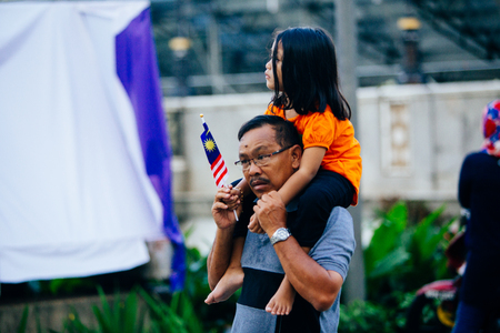 August 31st 2017, Kuala Lumpur Malaysia - A father carries his daughter on his back to watch the National Day celebration in Dataran Merdeka