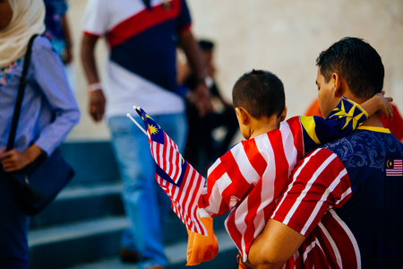 August 31st 2017, Kuala Lumpur Malaysia - A father carries his son to watch the National Day celebration in Dataran Merdeka Editorial