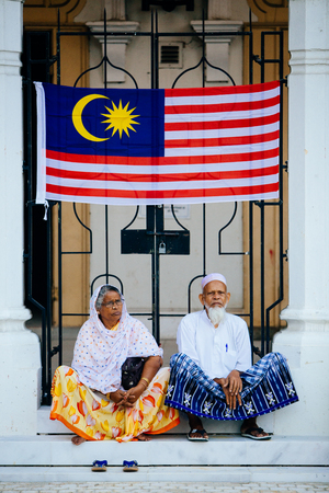 August 31st 2017, Kuala Lumpur Malaysia - Elderly couple sit in front of the Malaysian flag in conjunction with Malaysia Independence Day celebration near Dataran Merdeka